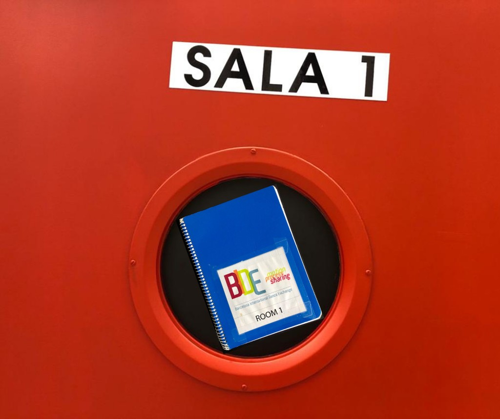 "Blue notebook in round window of red door ""Sala 1"""